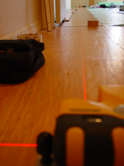 Precision laser alignment off existing 3 year old laminate installation in hallway. Now I can make the cuts along the wall and start installing the room. Quickstep laminate in Green Valley